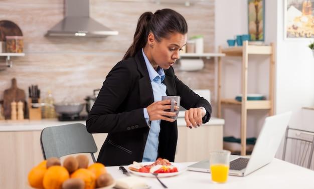Mulher de negócios caucasiana atrasada para o escritório pela manhã, comendo com pressa e olhando para o relógio