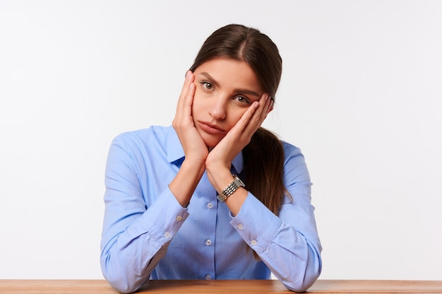 Mulher de negócios caucasiana chateada com merda azul sentada na mesa em branco isolado