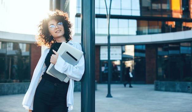 Mulher de negócios caucasiana com cabelo encaracolado e óculos posando do lado de fora com um laptop