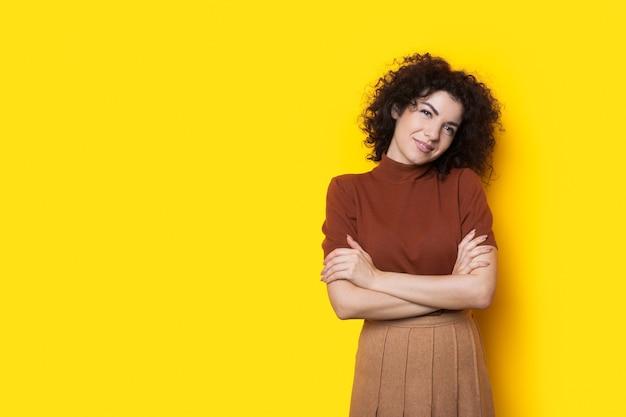 Mulher de negócios caucasiana com cabelo encaracolado posando com a mão cruzada em uma parede amarela com espaço livre