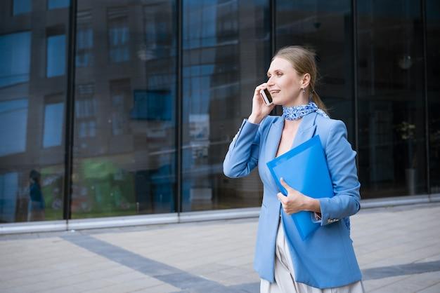 Mulher de negócios caucasiana com uma jaqueta azul e vestido falando ao telefone com uma pasta de papéis na mão contra a parede de um prédio de escritórios