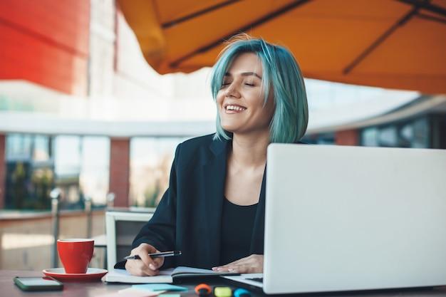 Mulher de negócios caucasiana de cabelos azuis está sorrindo em uma cafeteria, bebendo um chá e trabalhando no laptop