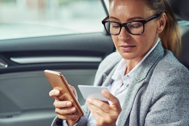 Mulher de negócios caucasiana de meia-idade sentada no banco de trás do carro olhando para um cartão de plástico em branco