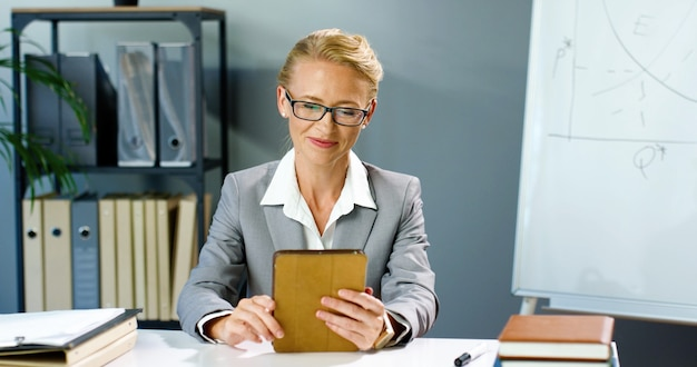 Mulher de negócios caucasiana em copos, sentado no escritório e falando via webcam no dispositivo tablet, videochat e educar negócios. vídeo blog de gravação de treinadora feminina no blogger videochat on-line no gadget