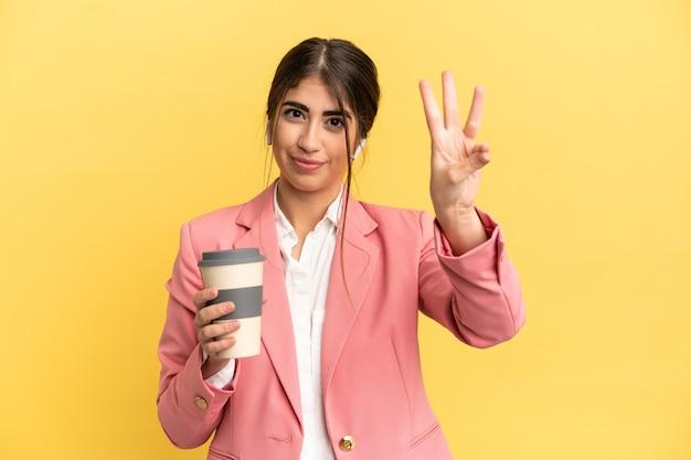 Mulher de negócios caucasiana isolada em um fundo amarelo feliz e contando três com os dedos