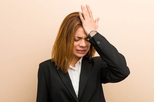 Mulher de negócios caucasiana jovem esquecendo algo, batendo na testa com a palma da mão e fechando os olhos.