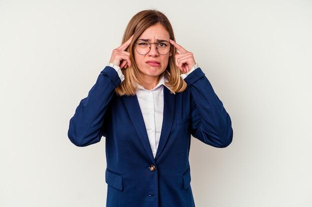 Mulher de negócios caucasiana jovem focada em uma tarefa, mantendo os indicadores apontando a cabeça.
