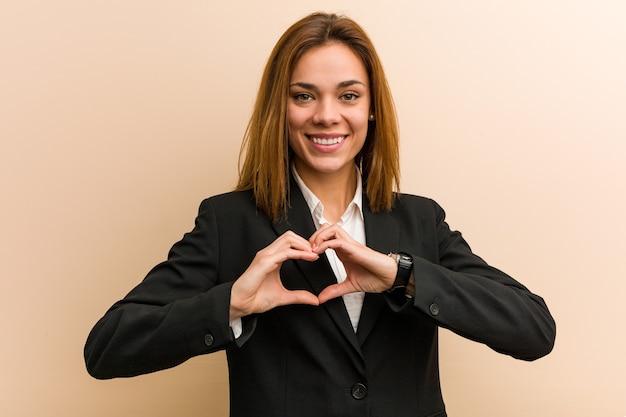 Mulher de negócios caucasiana jovem sorrindo e mostrando uma forma de coração com as mãos.