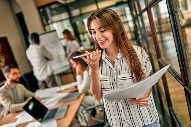 Mulher de negócios caucasiano alegre jovem falando ao telefone com documentos na mão em um escritório moderno. uma equipe de hipster de sucesso em um espaço de coworking. freelancers.
