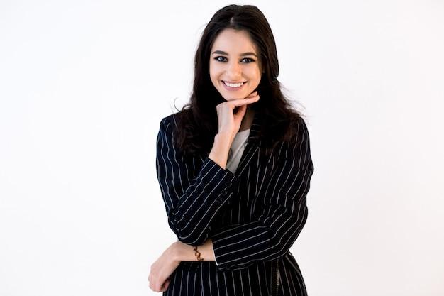Mulher de negócios caucasiano bonita sorridente na jaqueta preta com uma mão tocando o queixo