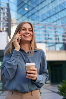 Mulher de negócios caucasiano falando por telefone segurando café para viagem. uma mulher europeia bem-sucedida, falando ao telefone, em um prédio de escritórios moderno