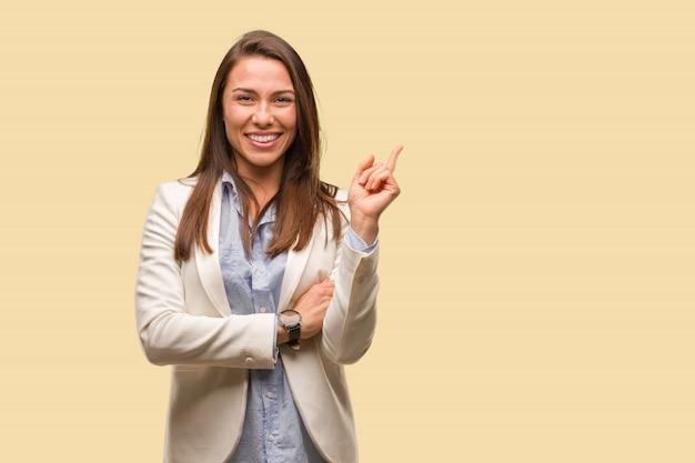 Mulher de negócios caucasiano jovem apontando para o lado com o dedo