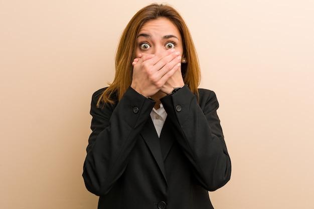 Mulher de negócios caucasiano jovem chocada cobrindo a boca com as mãos.