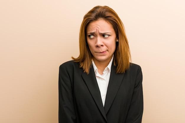 Mulher de negócios caucasiano jovem confusa, sente-se duvidoso e inseguro.