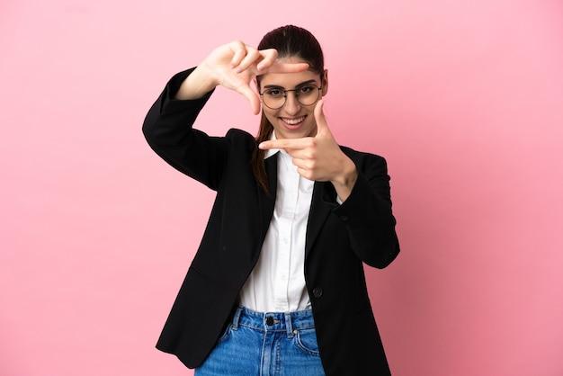 Mulher de negócios caucasiano jovem isolada no rosto de foco de fundo rosa. símbolo de enquadramento