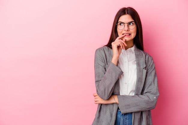 Mulher de negócios caucasiano jovem na rosa relaxada pensando em algo olhando para um espaço de cópia.