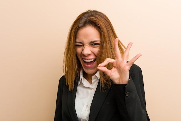 Mulher de negócios caucasiano jovem pisca um olho e mantém um gesto bem com a mão.