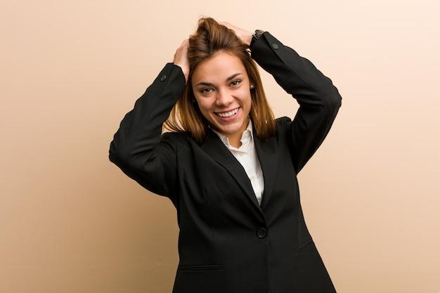 Mulher de negócios caucasiano jovem ri alegremente, mantendo as mãos na cabeça. conceito de felicidade.