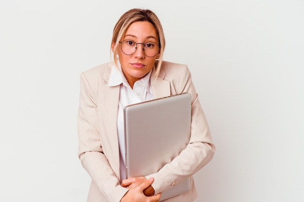 Mulher de negócios caucasiano jovem segurando um laptop isolado no fundo branco encolhe os ombros e abre os olhos confusos.