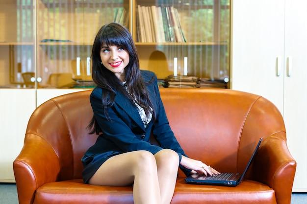 Mulher de negócios caucasiano nova bonita que trabalha no portátil.