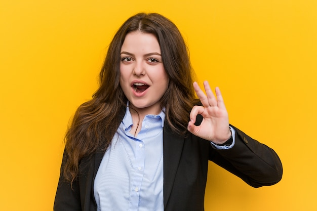 Mulher de negócios caucasiano plus size jovem pisca um olho e mantém um gesto bem com a mão