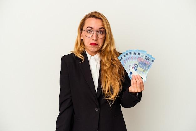 Mulher de negócios caucasiano segurando contas isoladas no fundo branco encolhe os ombros e abre os olhos confusos.