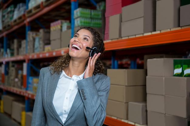 Mulher de negócios chamando com o fone de ouvido