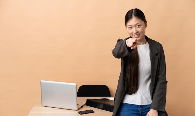 Mulher de negócios chinês em seu local de trabalho, apontando a frente com expressão feliz