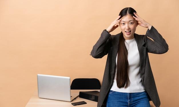 Mulher de negócios chinês em seu local de trabalho com expressão de surpresa