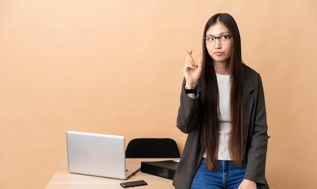 Mulher de negócios chinês em seu local de trabalho com os dedos cruzando e desejando o melhor
