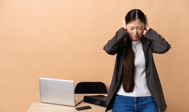 Mulher de negócios chinês em seu local de trabalho frustrado e cobrindo as orelhas