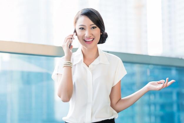 Mulher de negócios chinês em telefonema