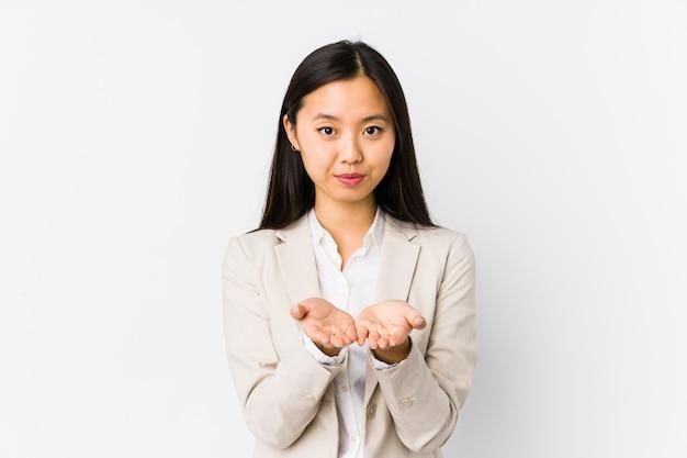 Mulher de negócios chinês jovem segurando algo com as palmas das mãos