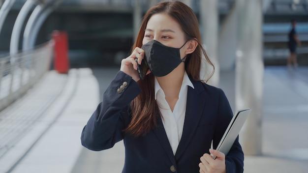Mulher de negócios chinesa andando e falando com o celular enquanto segura o laptop