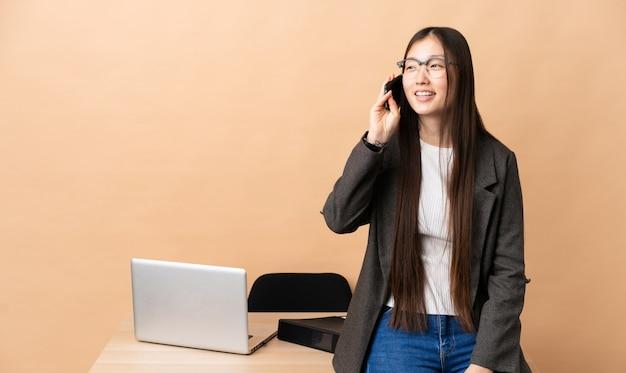 Mulher de negócios chinesa em seu local de trabalho, mantendo uma conversa com o telefone móvel