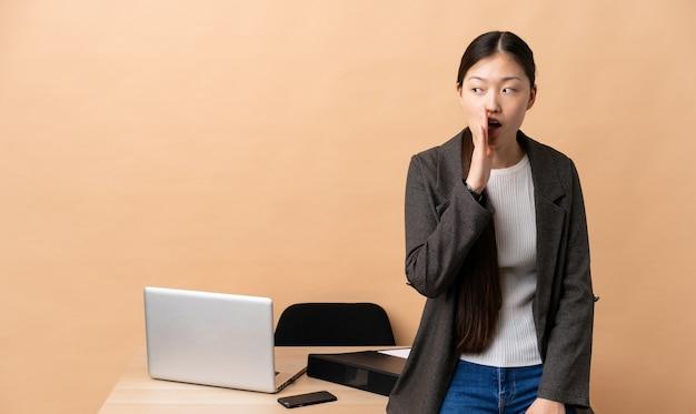 Mulher de negócios chinesa em seu local de trabalho sussurrando algo com gesto de surpresa enquanto olha para o lado