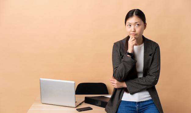 Mulher de negócios chinesa em seu local de trabalho, tendo dúvidas e pensando