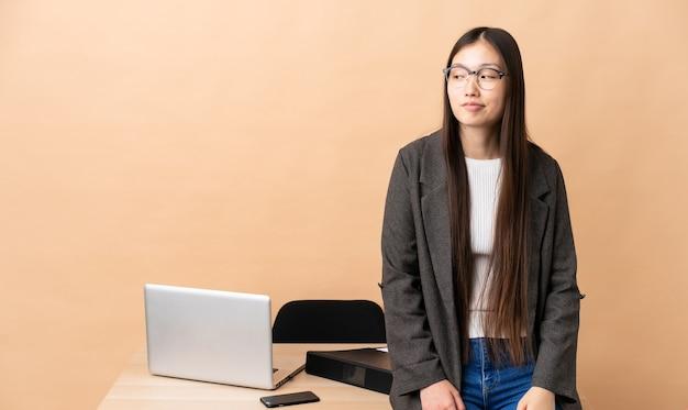 Mulher de negócios chinesa em seu local de trabalho tendo dúvidas enquanto olha de lado