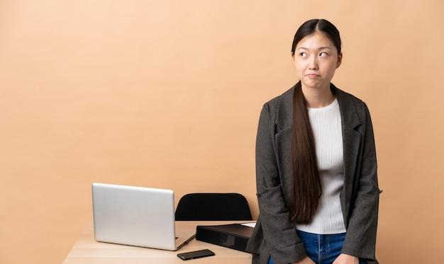 Mulher de negócios chinesa em seu local de trabalho tendo dúvidas enquanto olha para cima