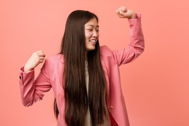 Mulher de negócios chinesa jovem vestindo terno rosa, comemorando um dia especial, salta e levantando os braços com energia.