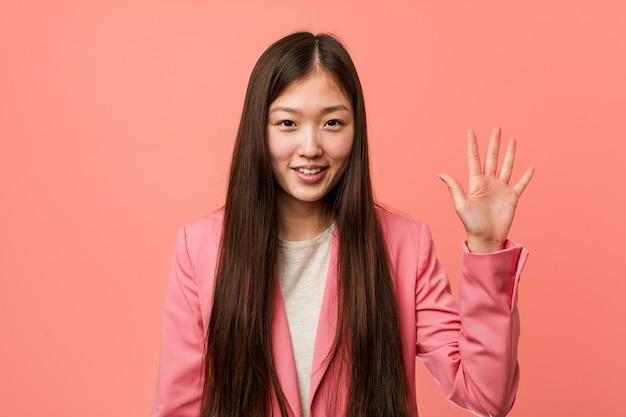 Mulher de negócios chinesa jovem vestindo terno rosa sorrindo alegre mostrando o número cinco com os dedos.