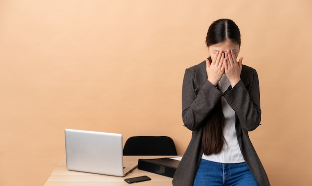 Mulher de negócios chinesa no local de trabalho com expressão cansada e doente