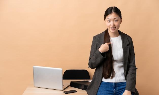 Mulher de negócios chinesa no local de trabalho com expressão facial surpresa