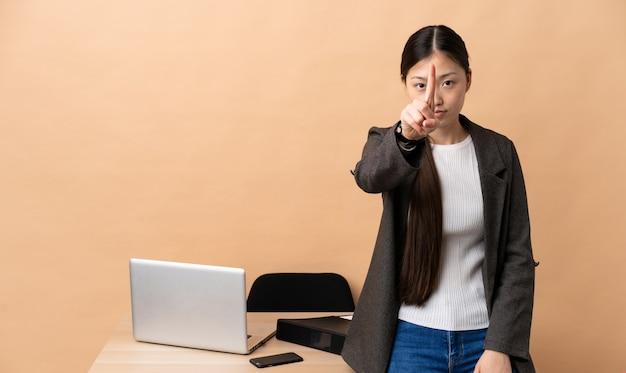 Mulher de negócios chinesa no local de trabalho contando uma com expressão séria