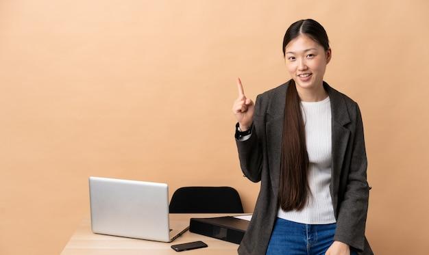 Mulher de negócios chinesa no local de trabalho mostrando e levantando o dedo em sinal dos melhores