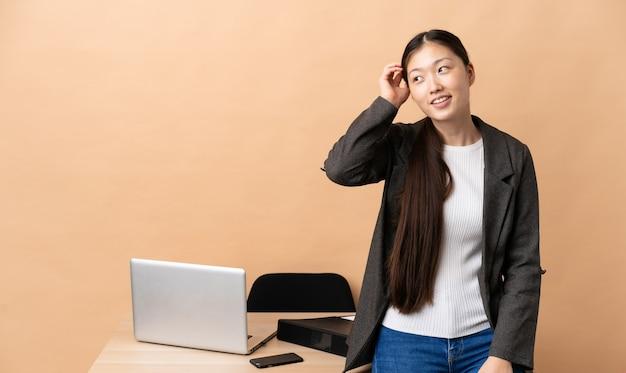 Mulher de negócios chinesa no local de trabalho, pensando em uma ideia
