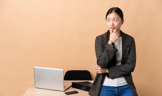 Mulher de negócios chinesa no local de trabalho, pensando uma ideia enquanto olha para cima