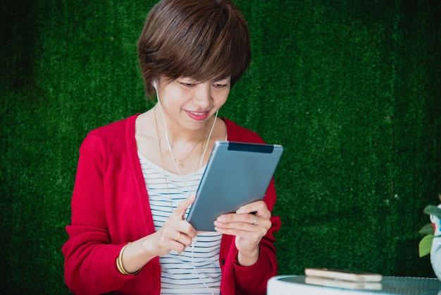 Mulher de negócios chinesa working on tablet computer fora do escritório. desgaste de mulher bonita camisa vermelha trabalhando ao ar livre.