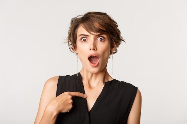 Mulher de negócios chocada apontando para si mesma ofendida