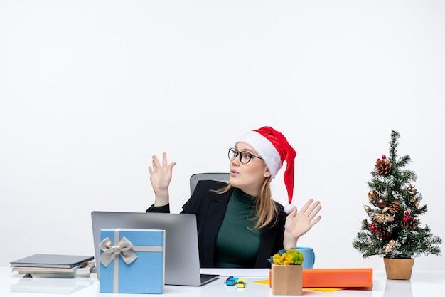 Mulher de negócios chocada com chapéu de papai noel, sentada à mesa com uma árvore de natal e um presente apontando para cima, sobre fundo branco